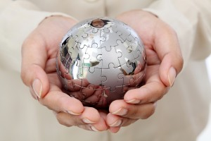Business woman hand holding jigsaw puzzle globe